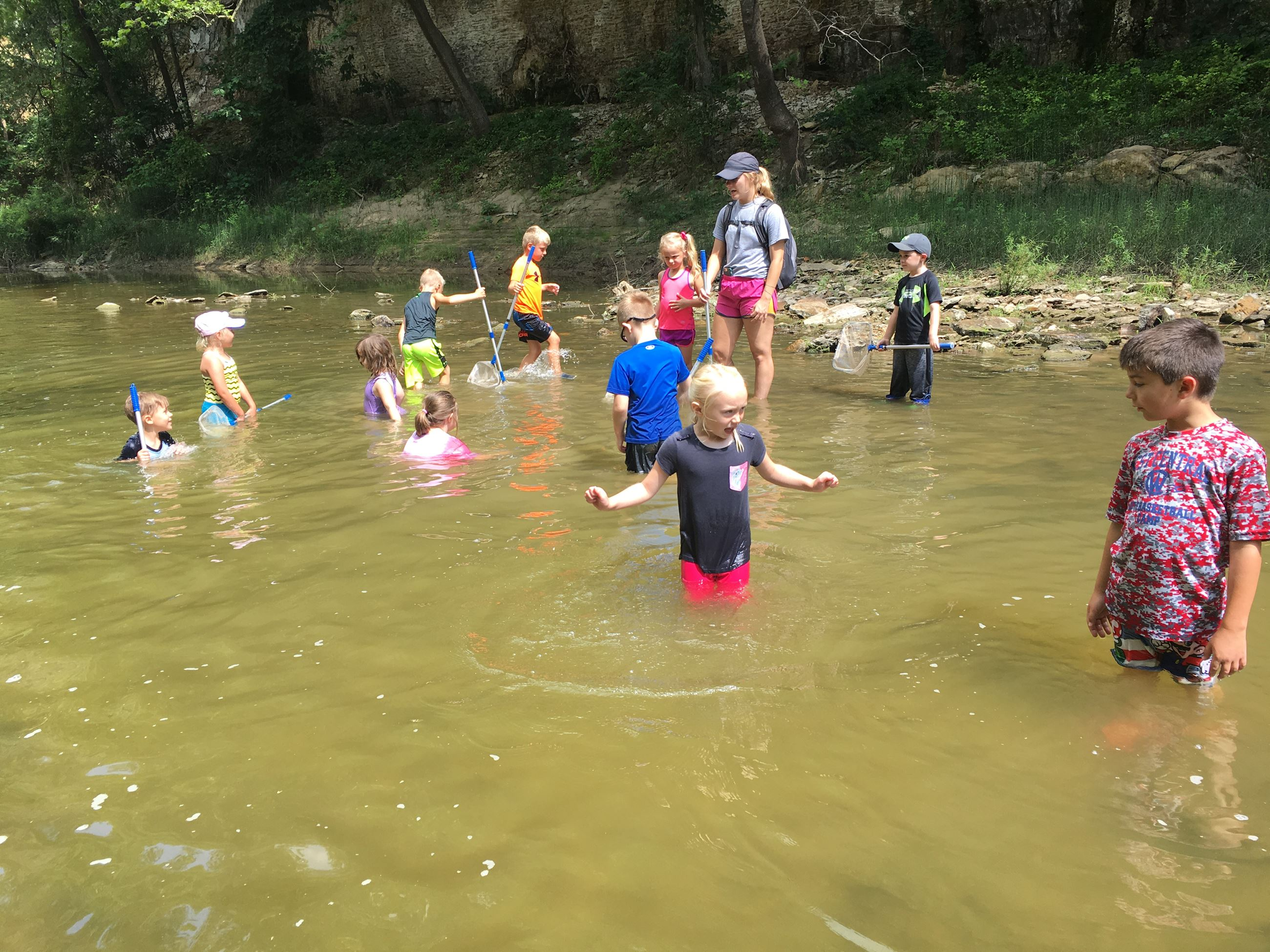 Kids playing in creek during DMCC summer camp.